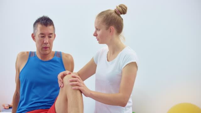 stockvideo's en b-roll-footage met slo mo vrouwelijke sportmassage therapeut masseren van een mannelijke cliënt knie en praten met hem - massagetafel