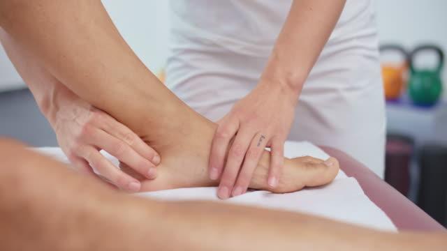 stockvideo's en b-roll-footage met slo mo vrouwelijke sportmassage therapeut masseren een problematisch gebied van de enkel van de klant - massagetafel