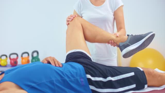 slo mo 女性スポーツ マッサージ セラピスト マッサージ 男性 選手の膝 - マッサージする点の映像素材/bロール