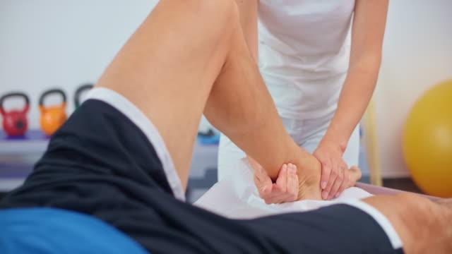 stockvideo's en b-roll-footage met slo mo vrouwelijke sportmassage therapeut werken aan de enkel van een cliënt - massagetafel