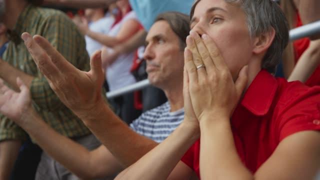 vídeos de stock e filmes b-roll de female sports fan sitting down on the stadium tribune in disappointment at the score - deceção