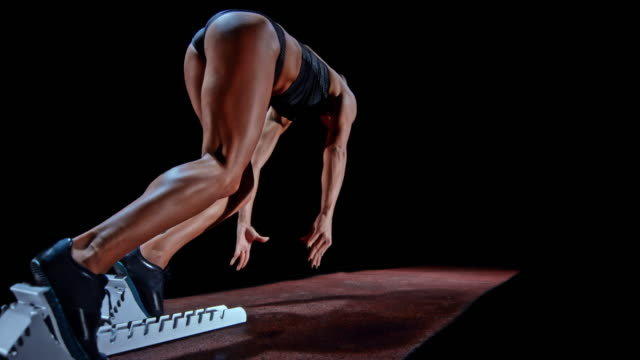vídeos de stock e filmes b-roll de slo mo female sprinter in black outfit starting from the starting block - mobilidade