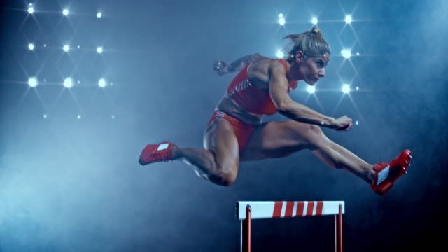 slo mo ds female sprinter jumping over a hurdle at night - track and field event stock videos and b-roll footage