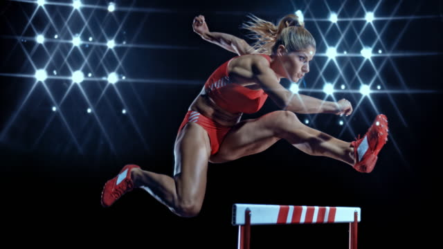 vídeos de stock, filmes e b-roll de slo mo ds female sprinter leaping over a hurdle at night - esforço