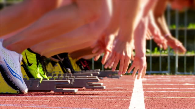 slo mo female sprinters pushing off of the starting block - competitive sport stock videos & royalty-free footage