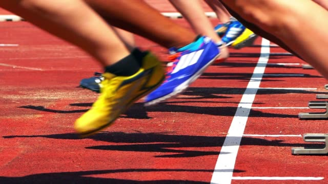 female sprinters starting from the starting block - pista di atletica leggera video stock e b–roll