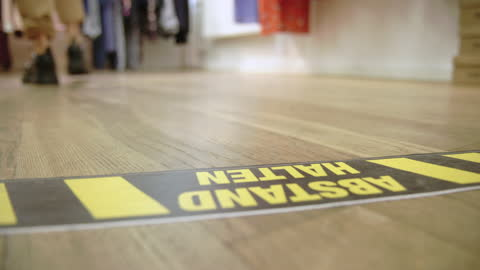 female standing at warning sign on floor in store - flooring stock videos & royalty-free footage