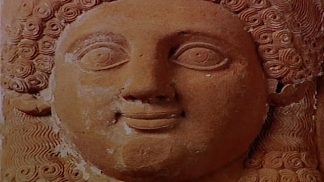 female stone sculpture. on face of ancient sculpture of an overweight female. - large stock videos & royalty-free footage