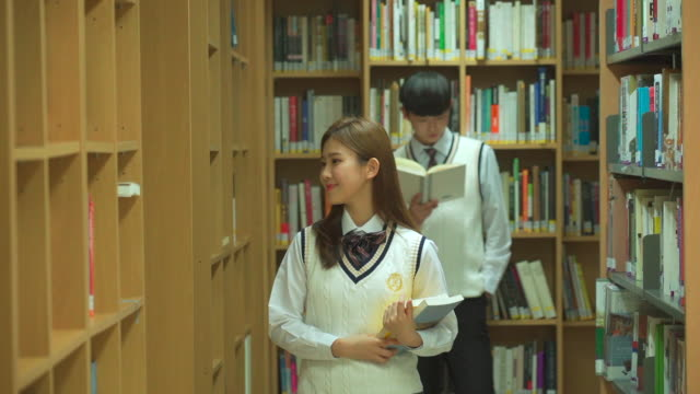 vídeos de stock e filmes b-roll de a female student and a male student reading books in the library - articulação humana