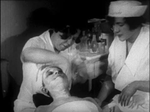 vídeos y material grabado en eventos de stock de b/w 1926 female student giving facial to / slapping face of woman in beauty school / newsreel - 1926