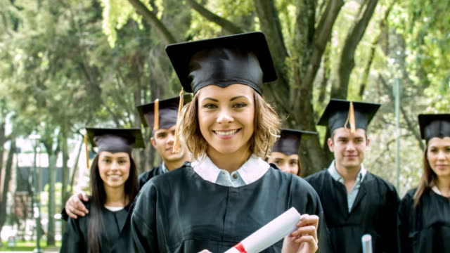 Female student holding her diploma on graduation day