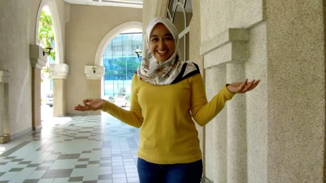 vídeos de stock, filmes e b-roll de aluna em hijab acolhedora e saudação - vestuário modesto