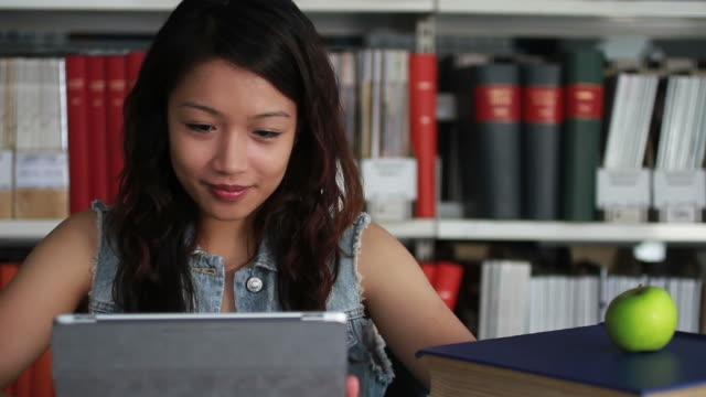 female student in library working on digital tablet - rucksack stock videos & royalty-free footage