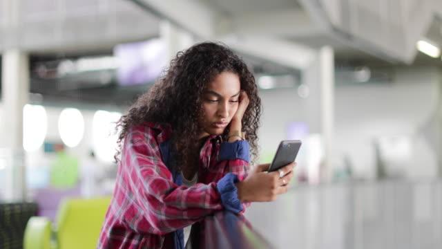 stockvideo's en b-roll-footage met female student looking at smartphone in high school - 14 15 jaar