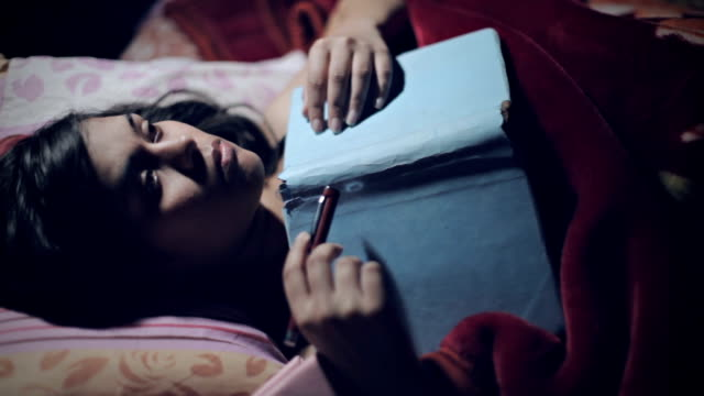 Female student lying on bed holding notebook and thinking.