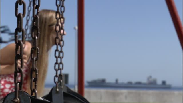 ms female student on childrens swing / cape town, western cape, south africa - ブランコ点の映像素材/bロール