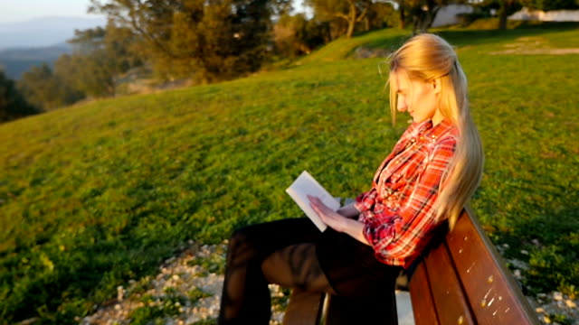 Female student reading book in park