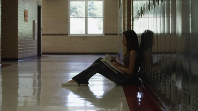 vídeos y material grabado en eventos de stock de ws zi female student (16-17) reading in school corridor / spanish fork city, utah, usa - sólo una adolescente