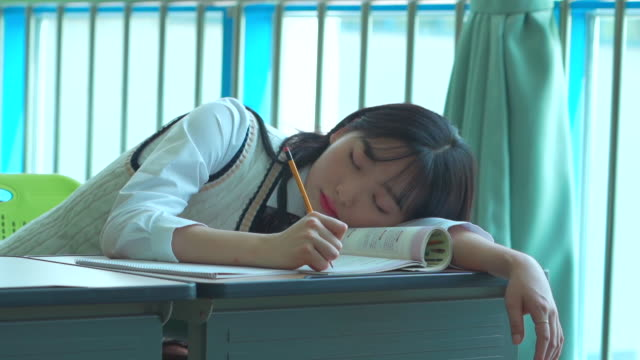 vidéos et rushes de a female student sitting and sleeping in the classroom - écolière