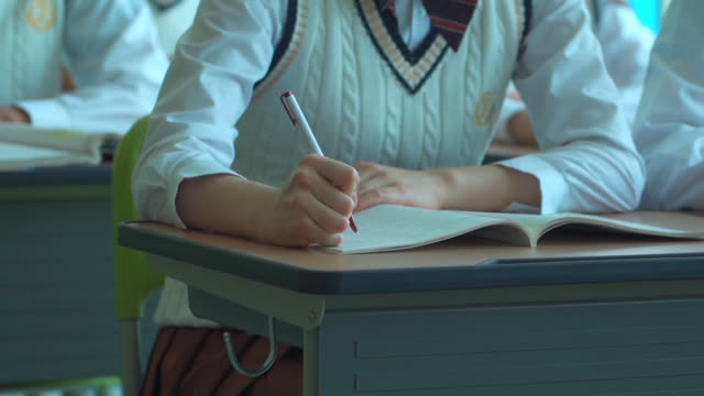 a female student sitting and writing on the textbook in the classroom - uniform stock videos & royalty-free footage