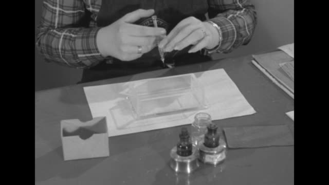 vidéos et rushes de female student sitting at table picks up hypodermic needle and fills it with litmus from small vial she then injects four sides of small transparent... - table top view
