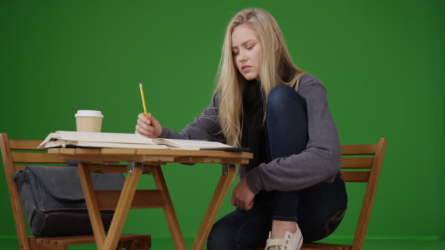 Female student sitting at table writing book report  on green screen