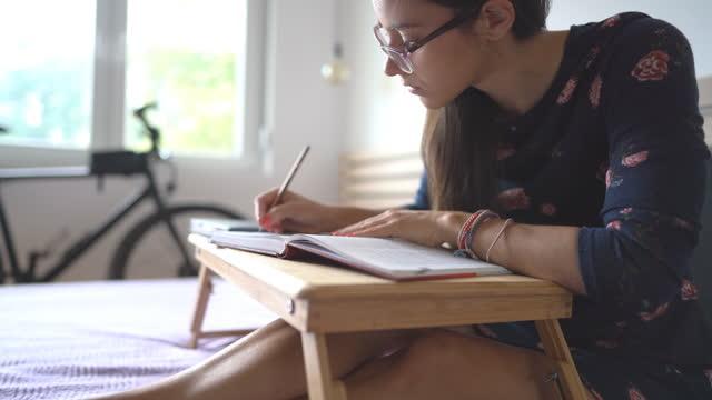 studentin sitzt auf dem bett und macht notizen mit bleistift - brille stock-videos und b-roll-filmmaterial