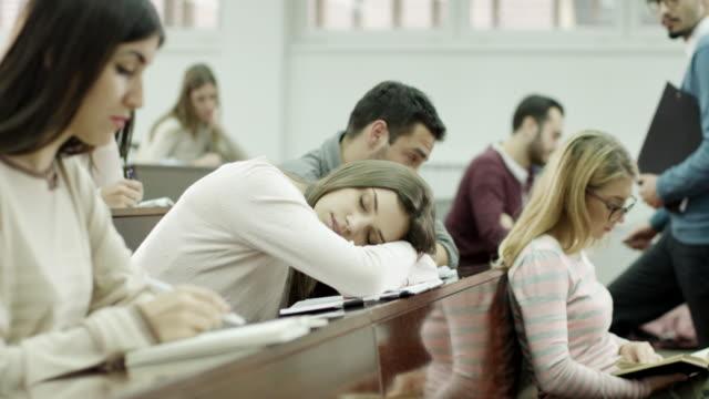 vídeos y material grabado en eventos de stock de estudiante mujer durmiendo en montaje tipo aula - person in further education