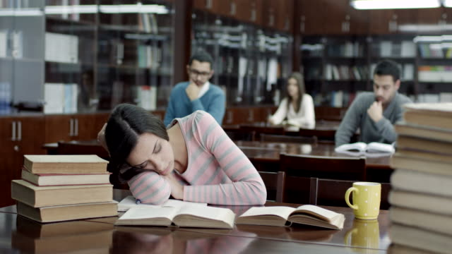 female student sleeping in library - snoring stock videos and b-roll footage