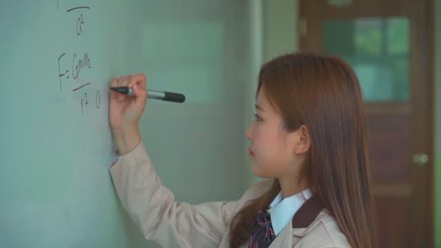 vídeos de stock e filmes b-roll de a female student solving a math problem on the board - aluna da escola secundária