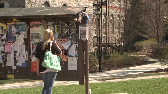 ms female student standing by notice board using mobile phone on campus, bethlehem, pennsylvania, usa - school bulletin board stock videos and b-roll footage