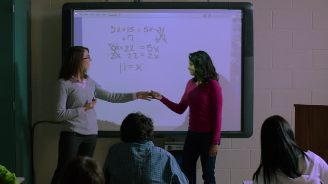 a female student successfully completes an equation on the smartboard for her class. - interactivity stock videos and b-roll footage