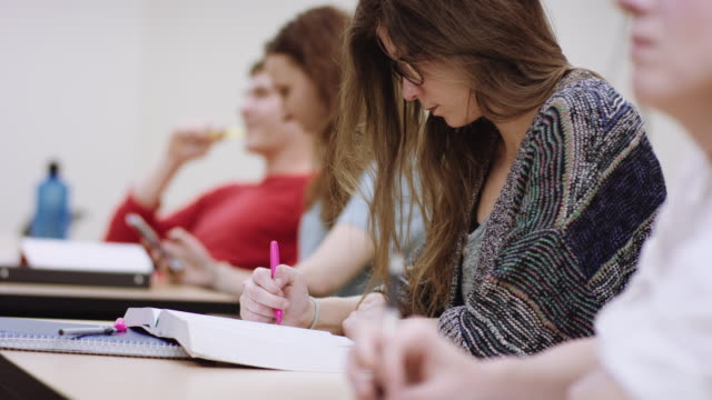 female student taking notes during a lecture - lecture hall stock videos & royalty-free footage