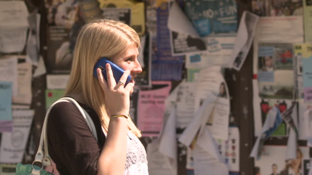 ms female student using mobile phone standing by notice board on campus, bethlehem, pennsylvania, usa - see other clips from this shoot 1503 stock videos and b-roll footage