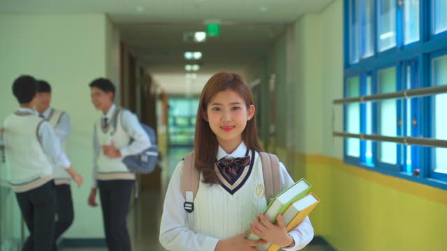 a female student walking and holding a book in the hallway of classroom - uniform stock videos & royalty-free footage