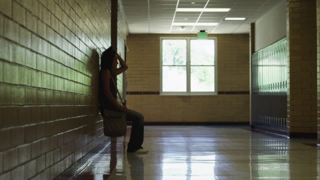 WS ZI Female student (16-17) walking and sitting down in school corridor / Spanish Fork City, Utah, USA