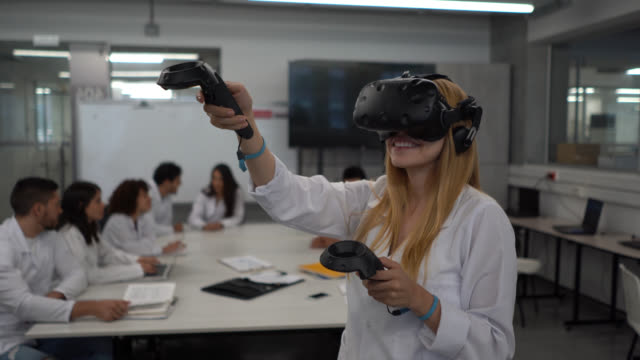 female student wearing a vr headset and holding joysticks during a lesson while other students sit at background around a table - cyberspace stock videos & royalty-free footage