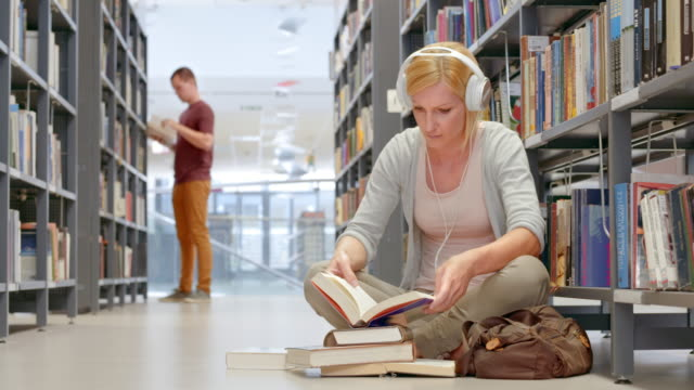 DS Female student wearing headphones browsing through books in library