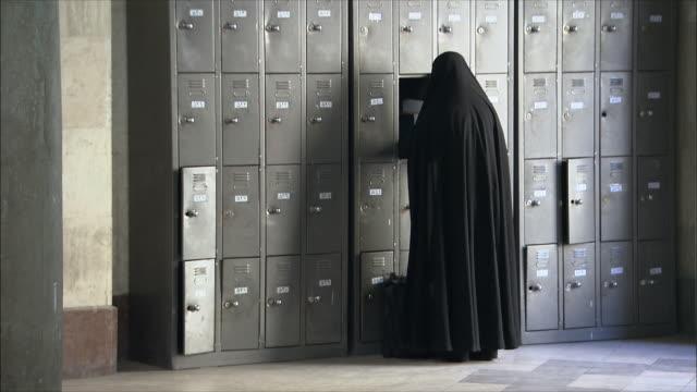 WS Female student wearing traditional clothing at locker, Tehran University, Iran