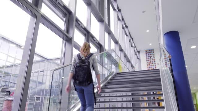 studentin mit rucksack geht oben in den klassenzimmer in der schule - steps and staircases stock-videos und b-roll-filmmaterial