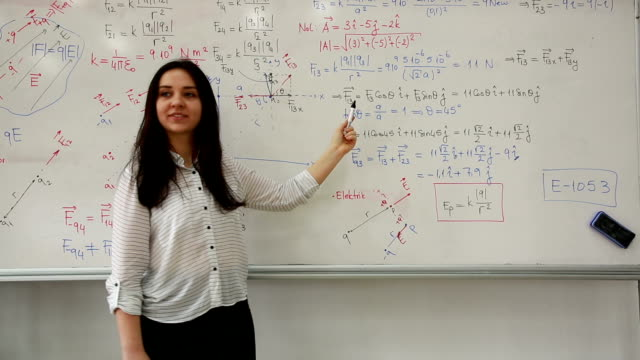 female student writing mathematical formula in front of the whiteboard - insegnante video stock e b–roll