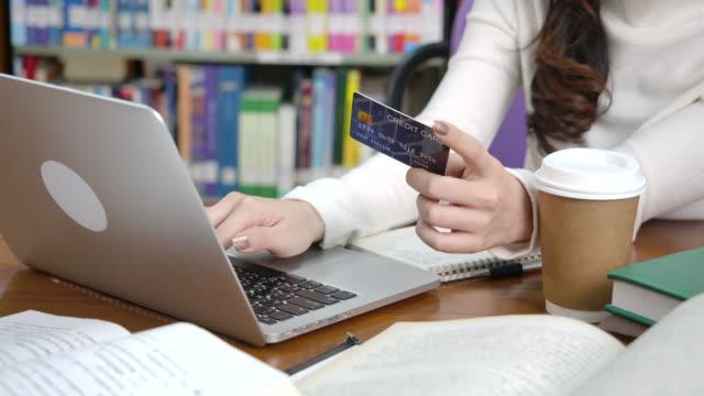 vídeos de stock e filmes b-roll de female students are using computers. order online and use credit cards - página da web