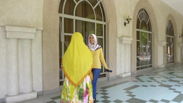 vídeos de stock, filmes e b-roll de estudantes do sexo feminino cumprimentando uns aos outros na área do campus - vestuário modesto
