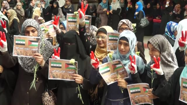 Female students of the Islamic University of Gaza attend a demonstration to show solidarity with Palestinian refugees living in Yarmouk Refugee Camp...