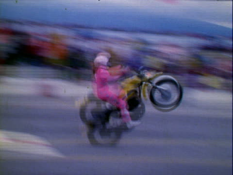 female stunt motorcycle rider wearing pink racing suit hitting ramp jumping suzuki 250 motorcycle over approximately 12 passenger cars at raceway... - verkehrsunfall stock-videos und b-roll-filmmaterial