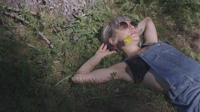 female sunbathing in countryside - liegen stock-videos und b-roll-filmmaterial