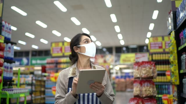 vídeos de stock e filmes b-roll de female supermarket employee or owner with face mask walking and using digital tablet - mercadoria