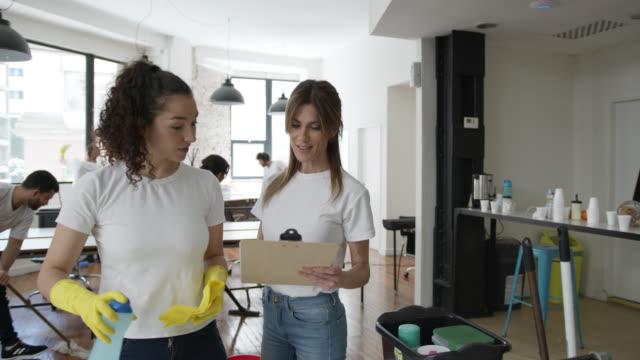 supervisore donna che parla con ogni membro del team mentre fa un servizio di pulizia in un ufficio - pulire video stock e b–roll