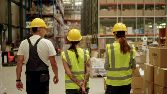 female supervisor walking on a warehouse with employees - recruitment stock videos & royalty-free footage