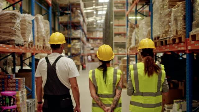 weiblichen vorgesetzten zu fuß auf einem lager mit mitarbeitern - korridor stock-videos und b-roll-filmmaterial